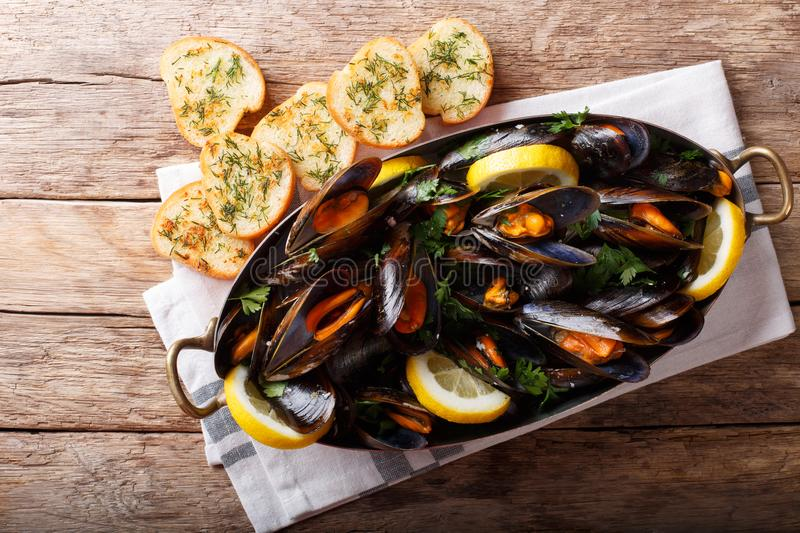 Copper pot of gourmet mussels with lemon, parsley and garlic served on a bread. horizontal top view stock photo