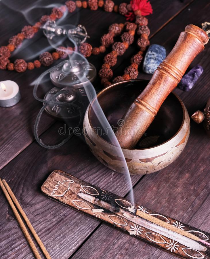 Copper singing bowl and a wooden stick on a brown table stock photo