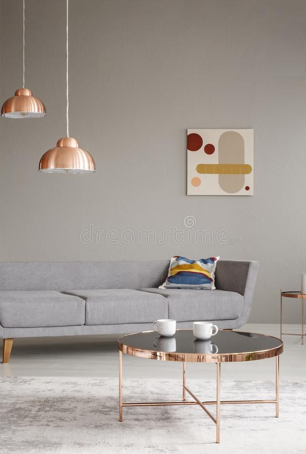 Copper table and lamps in a grey living room interior. Real photo stock photos