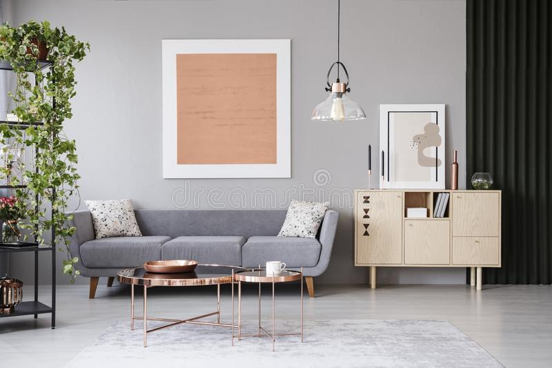 Copper tables in front of grey couch in modern apartment interior with painting and plant. Real photo. Concept stock photos
