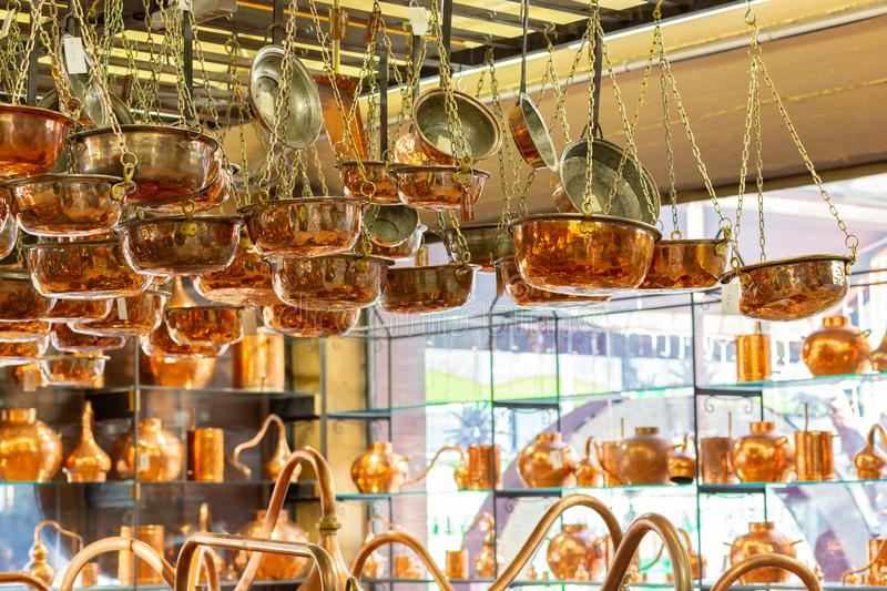 Copper ware, serpentine and jugs on the shop window in the store. stock image