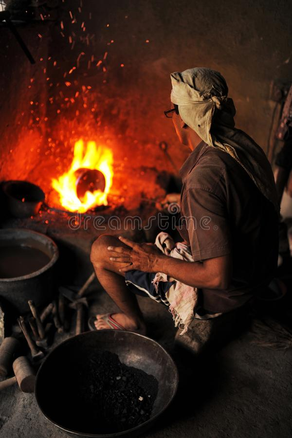 Coppersmith at work with fire at Tambat Ali,  Copper market,  Pune, India royalty free stock images