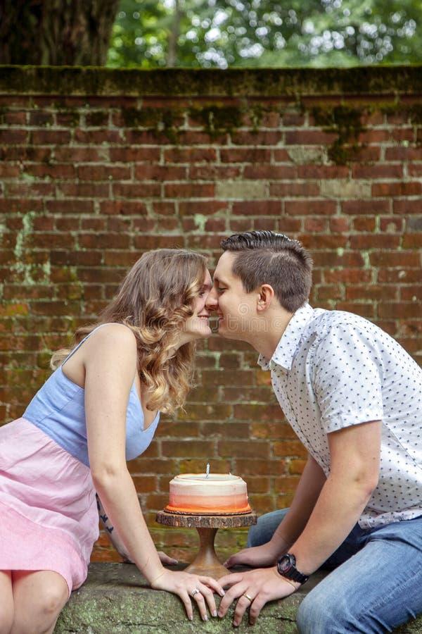 Coppia baciare sopra il dolce che celebra un anniversario di anno immagine stock libera da diritti