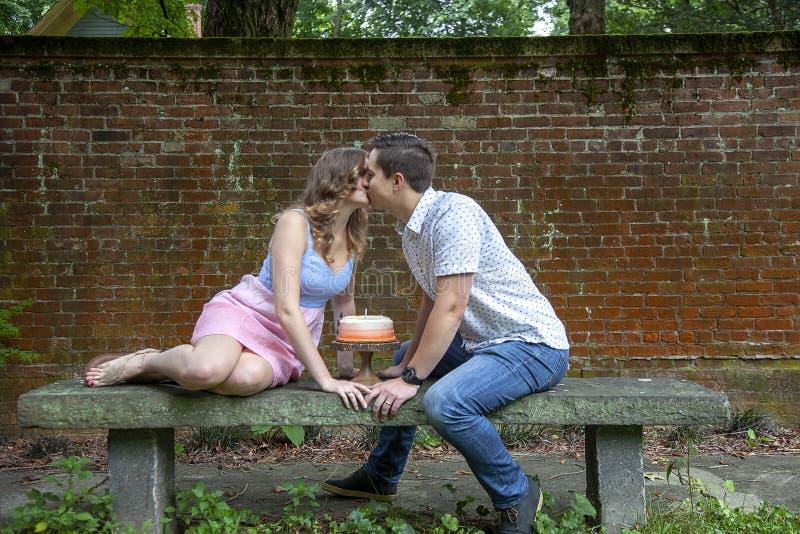 Coppia baciare sopra il dolce che celebra un anniversario di anno fotografie stock