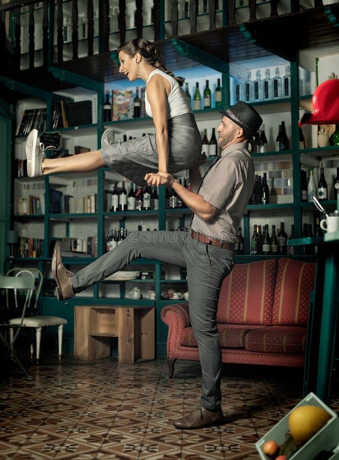Coppia ballare ed il salto in una stanza d'annata del caffè immagini stock