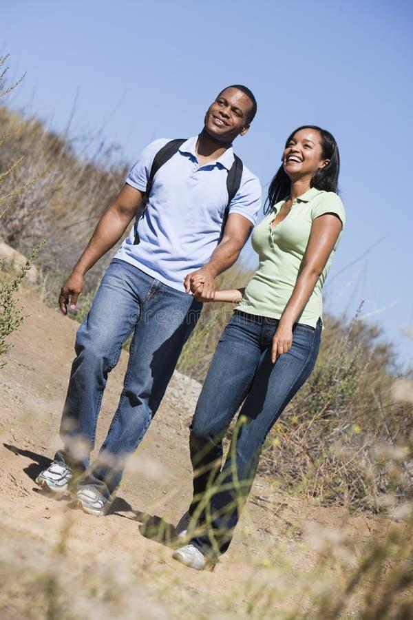 Coppia camminare sulle mani della holding del percorso e sorridere immagine stock