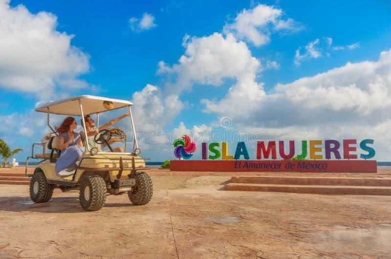 Coppia condurre un carretto di golf alla spiaggia tropicale su Isla Mujeres, Messico fotografia stock