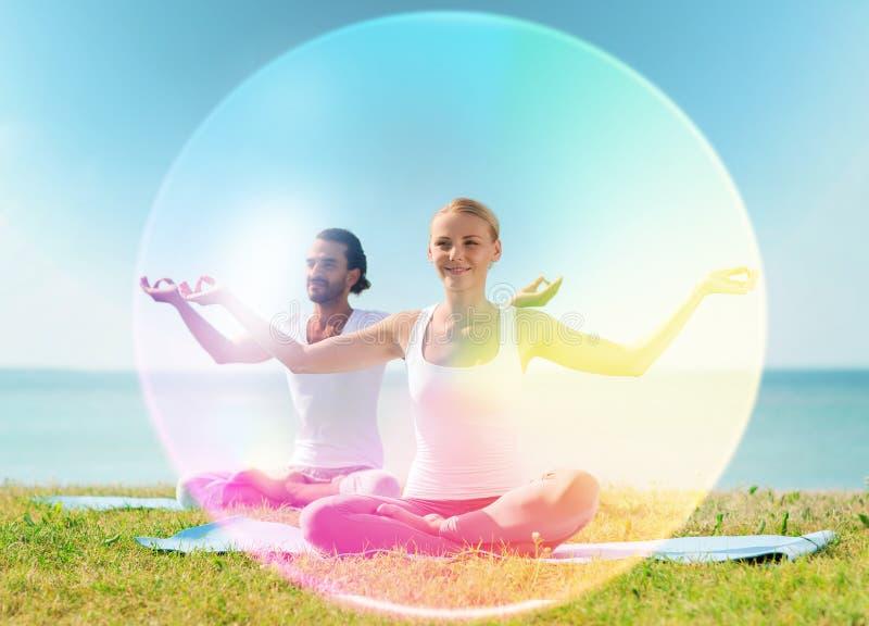 Coppia fare l'yoga nella posa del loto con aura dell'arcobaleno fotografie stock