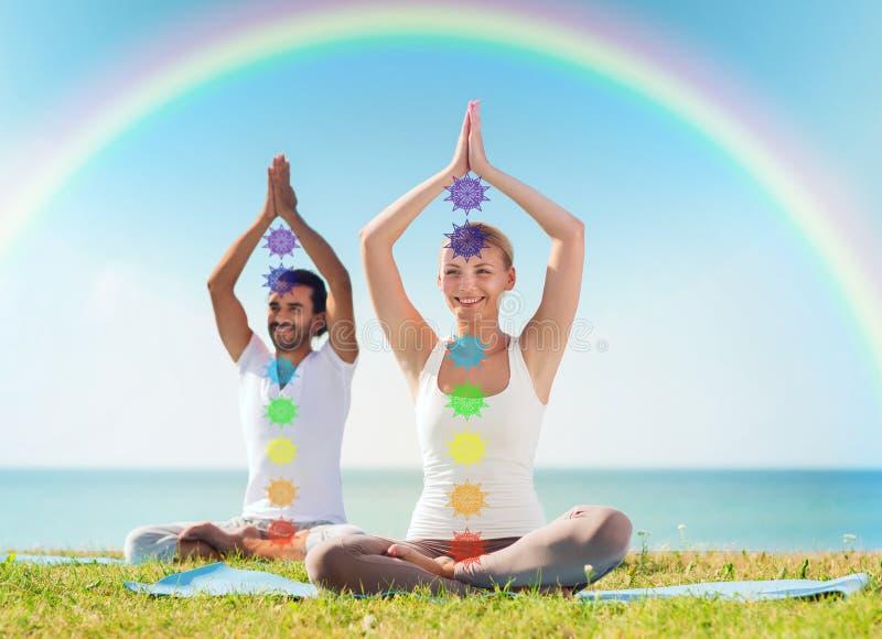Coppia fare l'yoga nella posa del loto con sette chakras fotografia stock libera da diritti