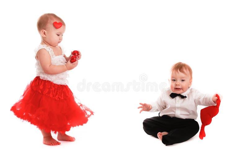 Coppia i bambini del ragazzo e della ragazza che giocano con il biglietto di S. Valentino di concetto dei cuori fotografie stock