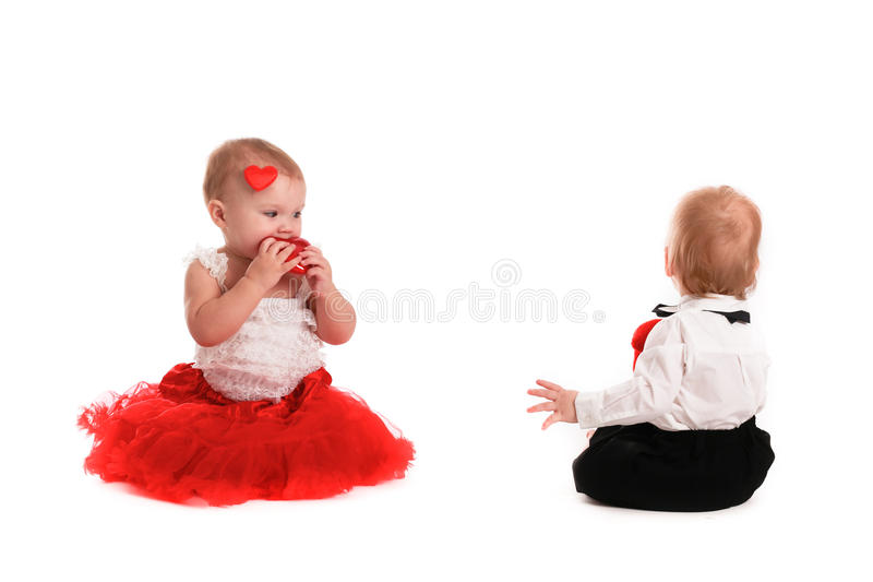 Coppia i bambini del ragazzo e della ragazza che giocano con il biglietto di S. Valentino di concetto dei cuori fotografia stock