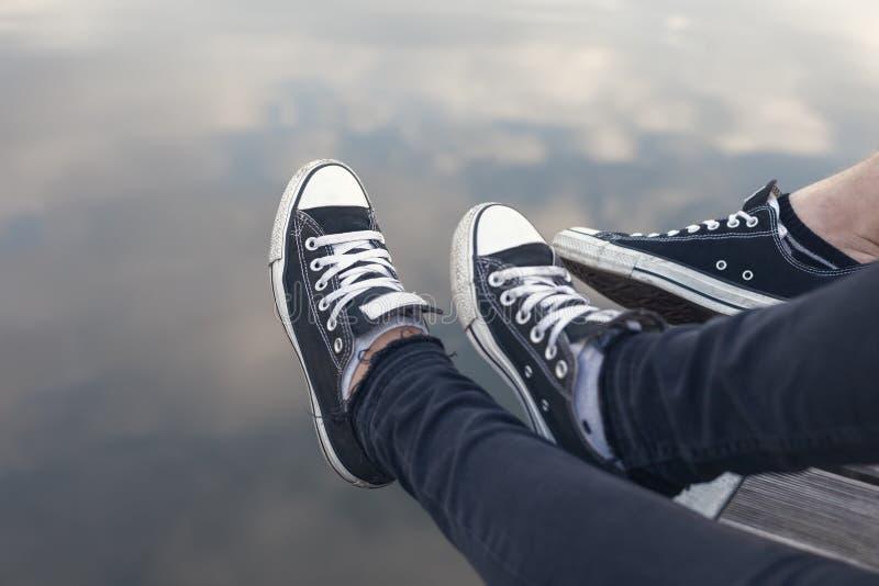 Coppia i piedi in scarpe da tennis che si rilassano dall'acqua fotografia stock libera da diritti