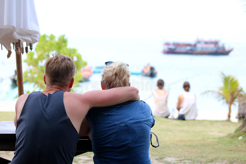 Coppia i turisti che godono delle viste di oceano sulla spiaggia immagine stock libera da diritti