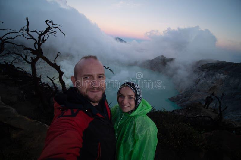 Coppia i viaggiatori che stanno sul bordo del vulcano di Ijen del cratere con il cielo variopinto alla mattina immagini stock