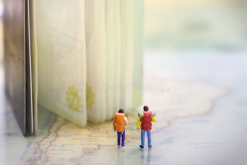 Coppia i viaggiatori con zaino e sacco a pelo/viaggiatori che stanno sulla mappa di mondo d'annata con il passaporto immagine stock libera da diritti