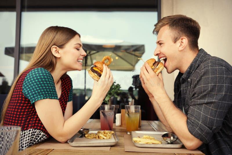 Coppia il cibo degli hamburger in caffè della via immagine stock
