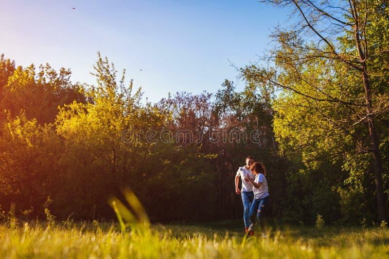 Coppia il funzionamento e divertiresi nell'uomo della foresta di primavera che prova a prendere la sua amica fotografia stock libera da diritti