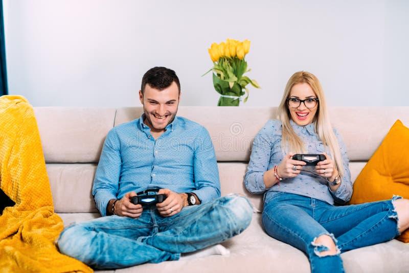 Coppia il gioco dei video giochi digitali con il regolatore della leva di comando mentre si siedono sul sofà o sullo strato immagine stock