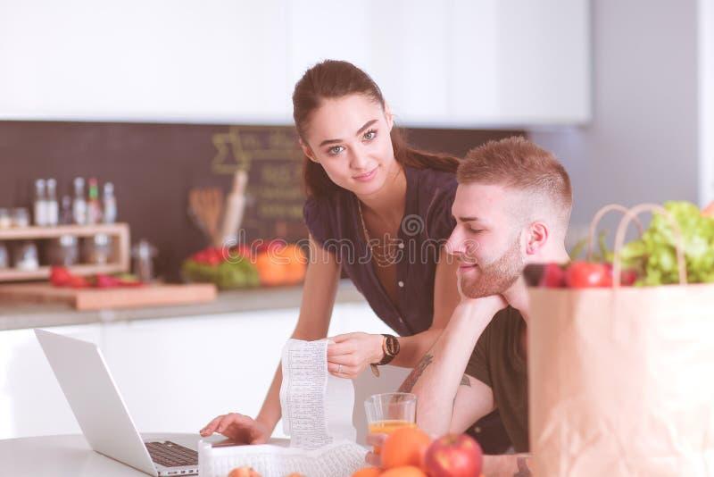 Coppia il pagamento delle loro fatture con il computer portatile in cucina a casa fotografia stock