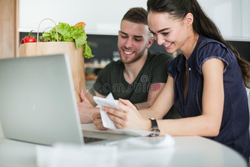 Coppia il pagamento delle loro fatture con il computer portatile in cucina a casa immagine stock libera da diritti