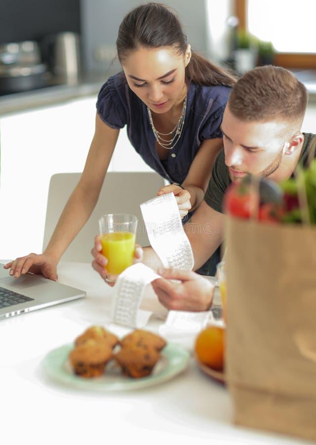 Coppia il pagamento delle loro fatture con il computer portatile in cucina a casa fotografia stock libera da diritti