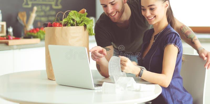 Coppia il pagamento delle loro fatture con il computer portatile in cucina a casa immagini stock