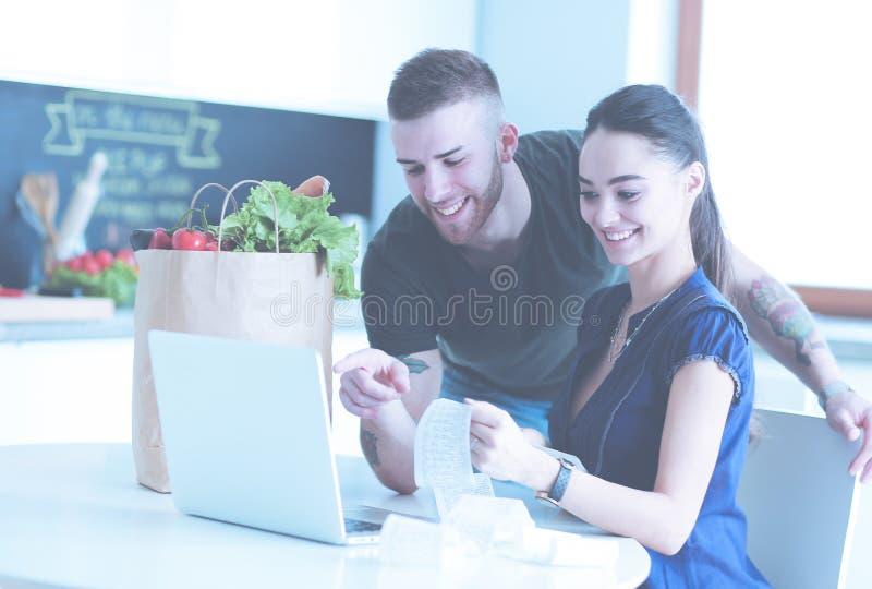 Coppia il pagamento delle loro fatture con il computer portatile in cucina a casa immagini stock libere da diritti