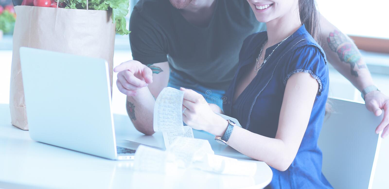 Coppia il pagamento delle loro fatture con il computer portatile in cucina a casa immagine stock