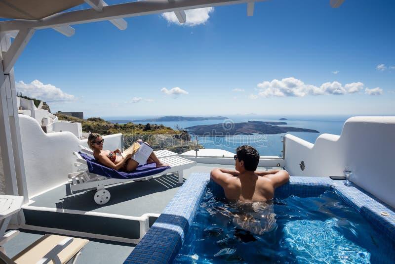 Coppia il rilassamento e la contemplazione della scena bella dalla piscina privata in una di OIA, Santorini, Grecia immagine stock