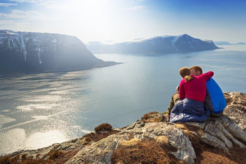 Coppia il riposo sulla collina di Sukkertoppen con la vista del fiordo in Norvegia immagine stock libera da diritti