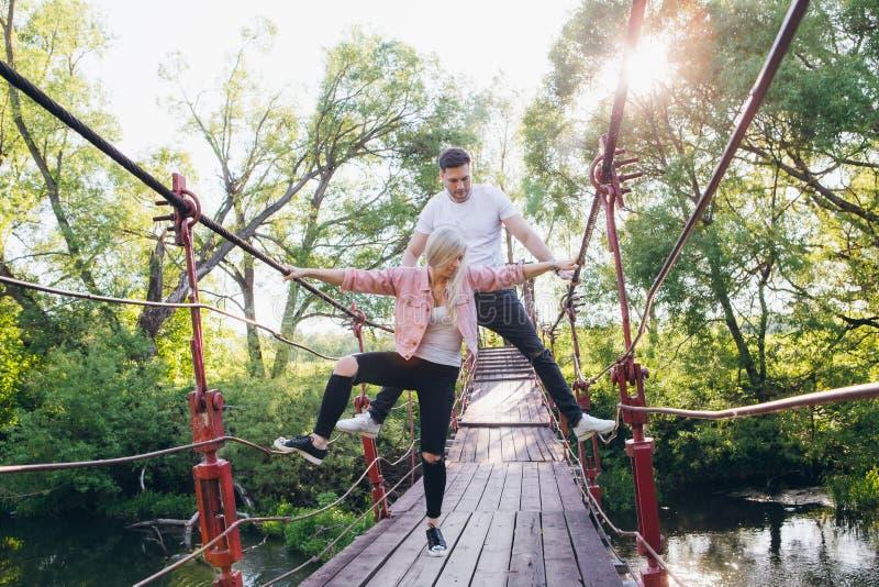 Coppia il tipo e la ragazza sul ponte sopra il fiume che imbroglia intorno fotografia stock