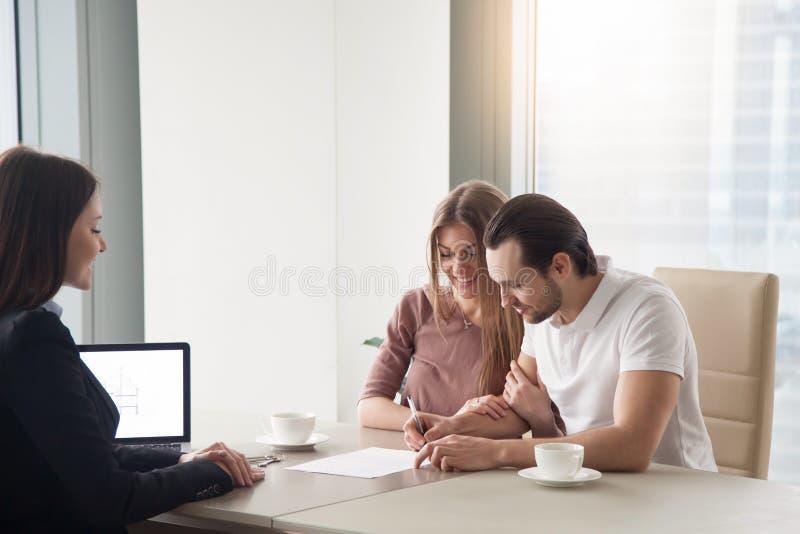 Coppia l'acquisto, affittando l'appartamento, firmante il contratto di accordo fotografia stock libera da diritti