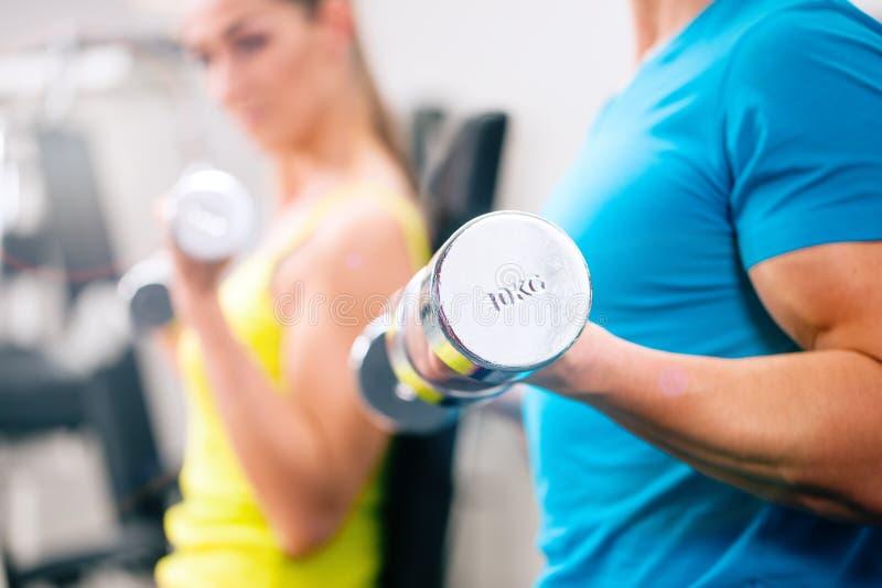 Coppia l'addestramento per la forma fisica in palestra con i pesi immagine stock
