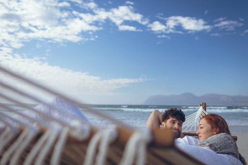Coppia l'interazione a vicenda mentre si rilassano all'amaca fotografia stock libera da diritti