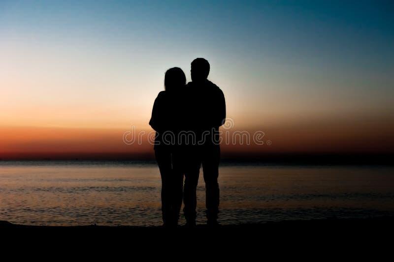 Coppia l'uomo e la donna che abbracciano nell'amore che resta sulla spiaggia immagine stock libera da diritti
