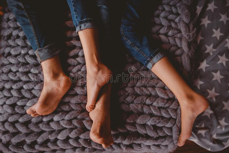 Coppia l'uomo e la ragazza che si trovano in pantaloni dei vestiti blu sul letto fotografia stock libera da diritti