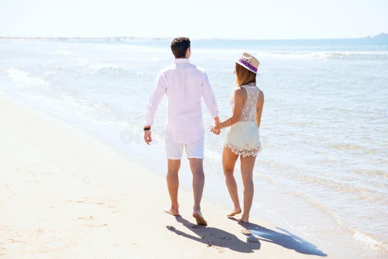 Coppia la camminata alla spiaggia un giorno soleggiato immagine stock