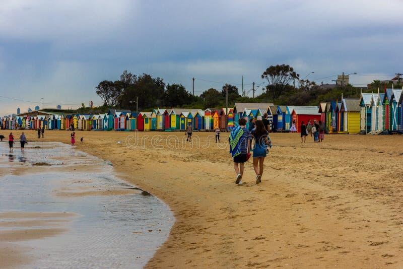 Coppia la camminata lungo Brighton Bathing Boxes, uno dei posti popolari di viaggio dell'attrazione a Melbourne, situato sulla sp fotografia stock
