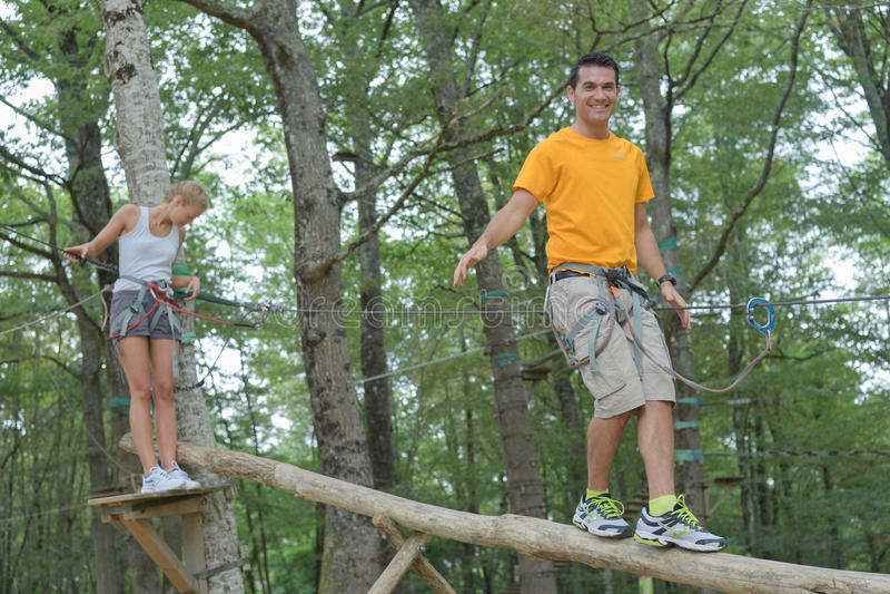 Coppia la camminata sul tronco sospeso al parco di avventura fotografie stock