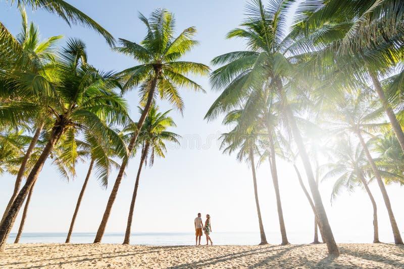 Coppia la condizione sulla spiaggia sabbiosa fra le palme sulla mattina soleggiata fotografie stock libere da diritti