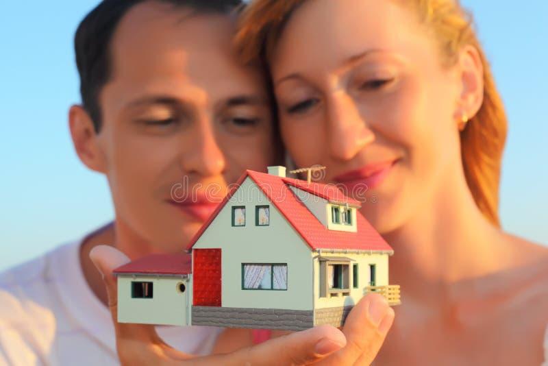 Coppia la conservazione nel modello delle mani della casa con il garage fotografia stock