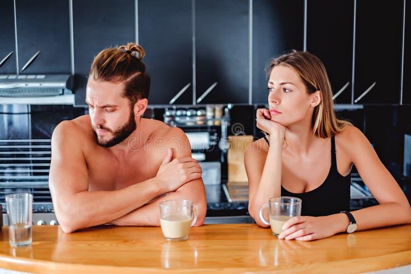 Coppia la conversazione mentre si siedono nella cucina fotografia stock libera da diritti