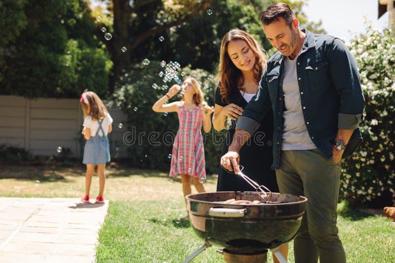 Coppia la cottura dell'alimento arrostito in cortile con il gioco dei bambini fotografia stock libera da diritti