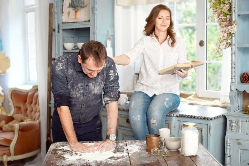Coppia la lettura del libro delle ricette per cucinare alcuni piatti immagini stock
