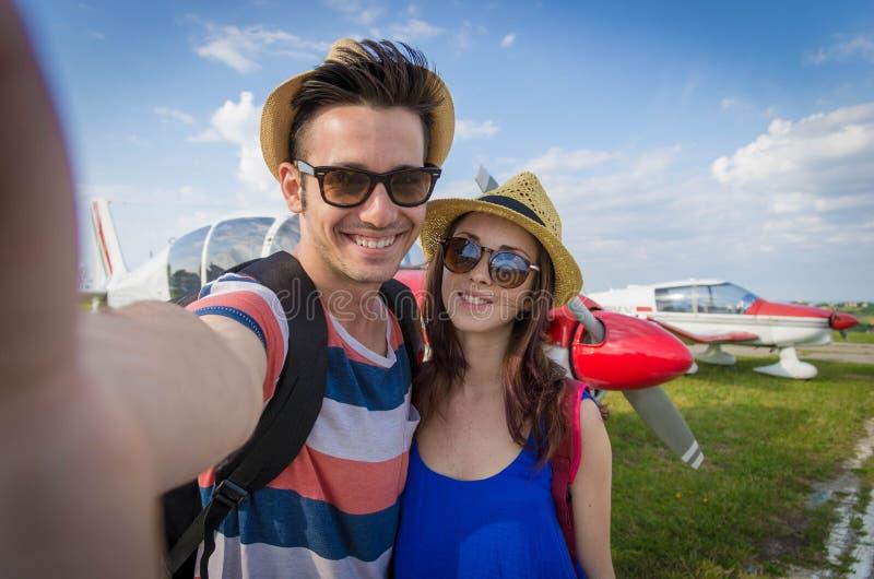 Coppia la presa del selfie all'aeroporto sulla vacanza fotografia stock