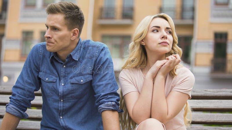 Coppia la rottura su, l'uomo turbato e la donna gridare che si siedono sul banco, divorzio fotografie stock