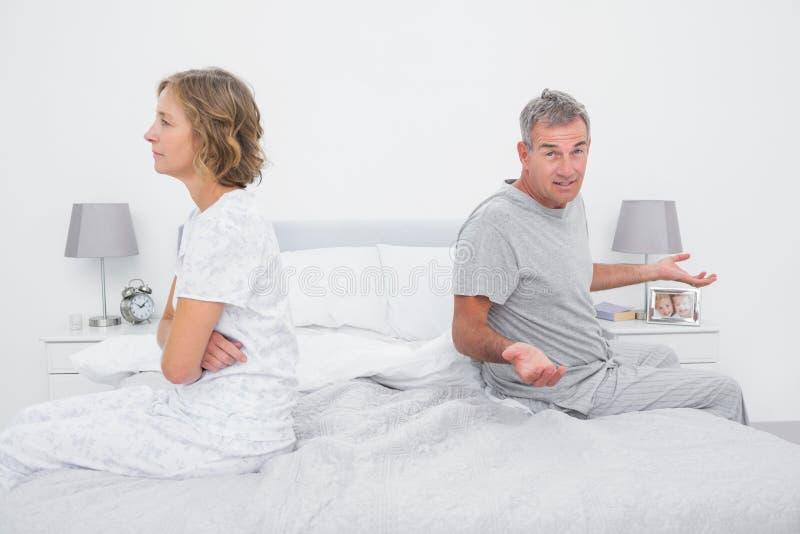 Coppia la seduta dai lati differenti del letto che ha una disputa immagine stock