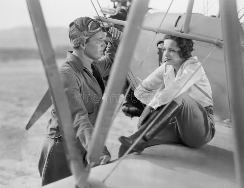 Coppia la seduta insieme su un aereo che se esamina (tutte le persone rappresentate non sono vivente più lungo e nessuna propriet fotografia stock libera da diritti