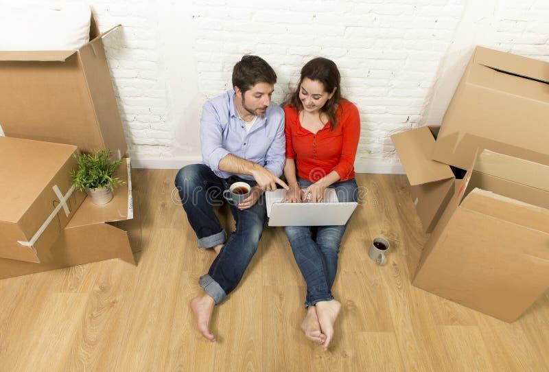 coppia la seduta sul pavimento che si muove nella nuova casa che sceglie la mobilia con il computer portatile del computer fotografie stock libere da diritti