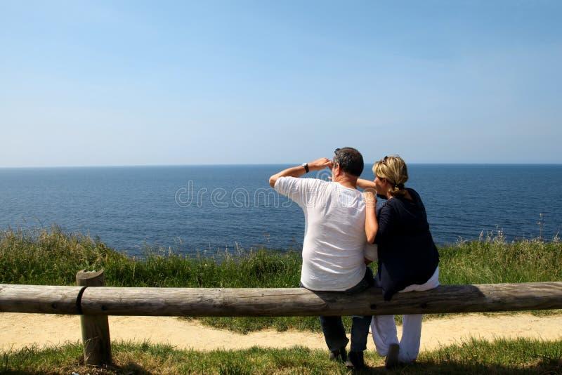 Coppia la seduta sul recinto e sulla vista dell'oceano piena d'ammirazione immagine stock libera da diritti